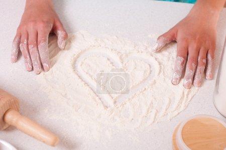 Photo pour Forme de coeur sur la farine, fait par les mains de la femme . - image libre de droit