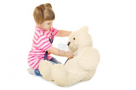 Little girl listens a stethoscope to a toy bear