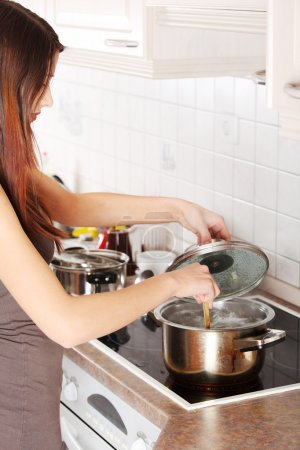 Photo for Young woman cooking in her kitchen - Royalty Free Image