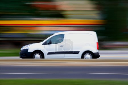 Speedy white minivan is going on road