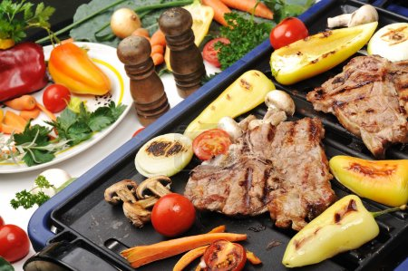 Barbecue, prepared beef meat and different vegetables and mushrooms on gril