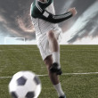 Football player on field playing with a ball...
