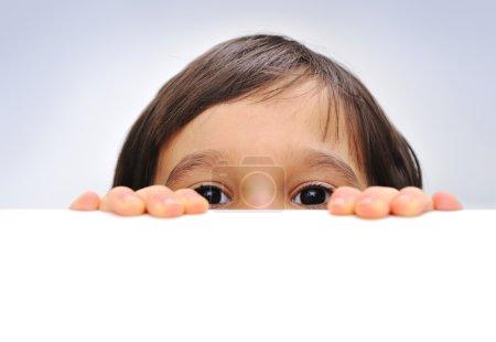 Photo pour Enfant tenant un signe vide sur un fond blanc, se cachant derrière - image libre de droit