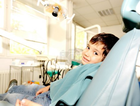 At dentist's modern working place, cute kid sitting on chair and smili