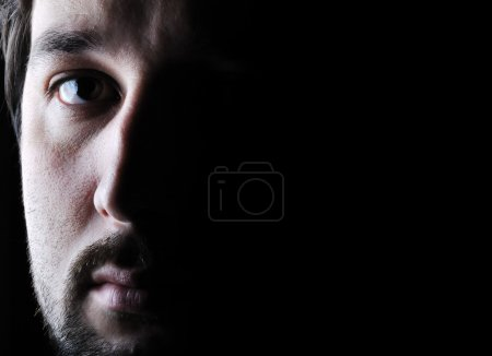 Photo for Low-key portrait - half face - sad and angry looking man - Royalty Free Image