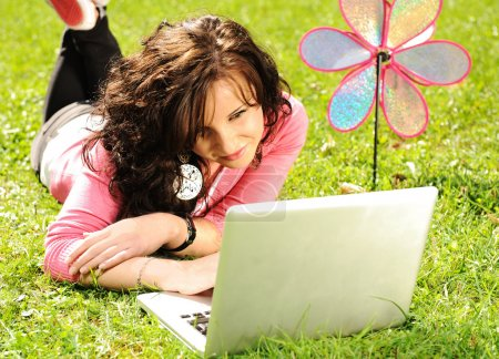 Happy young girl laying on green grass in nature and working on laptop