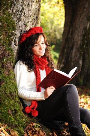 Photo pour Beauté magnifique automne fille assis dans la nature à côté de l'arbre et la lecture du livre et le claquement - image libre de droit