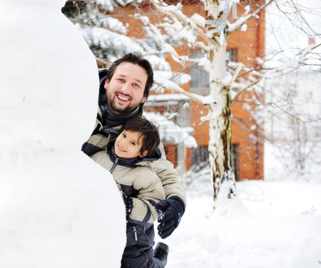Father and son playing happily in snow making snowman, winter season