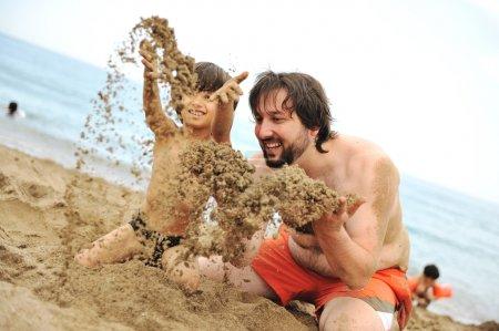 gra razem w piasku na plaży, młody ojciec i małego synka