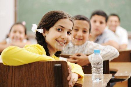 Photo pour Enfants heureux mignons en salle de classe avec leur professeur - image libre de droit