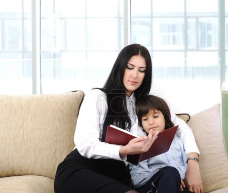 Mother and a son reading a book at home