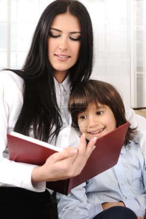 Mother and a son reading a book at home, closeup