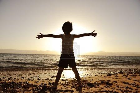 Photo pour Silhouette d'enfant sur la plage, les mains en l'air, vers le soleil - image libre de droit