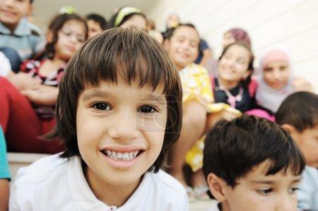 Photo pour Foule d'enfants, de différents âges et races devant l'école, la récréation - image libre de droit