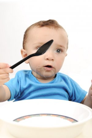Cute adorable one year old baby with green eyes eating on table, spoon and
