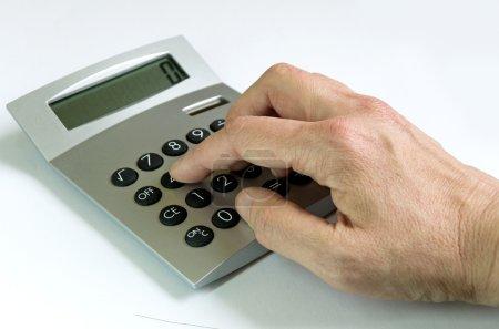 Photo pour Main à l'aide d'une calculatrice en face de fond blanc - image libre de droit