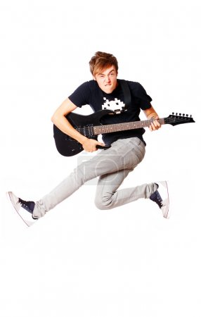 Young teenager jumping with guitar