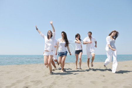 Group of happy young in have fun at beach