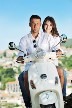 Portrait of happy young love couple on scooter enjoying summer t