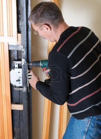 Handyman repairing lock