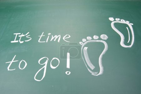 Photo for It is time to go! hand writing footprints and words on blackboard - Royalty Free Image