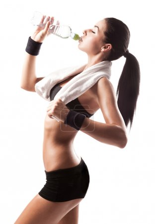 Photo for Sporty muscular woman drinking water, isolated against white background - Royalty Free Image