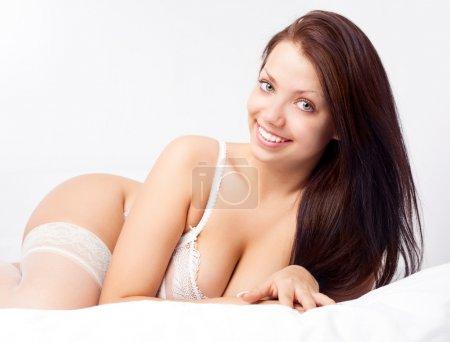 Photo pour Sexy jeune femme brune portant des sous-vêtements sur le lit à la maison - image libre de droit