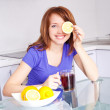 Pretty young woman drinking black tea with lemons in the kitchen at home