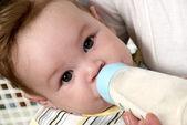 Portrait baby drinking milk of her bottle