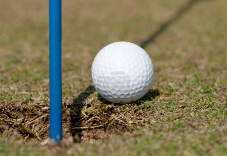 Golf ball on lip of cup of lovely tropical golf course