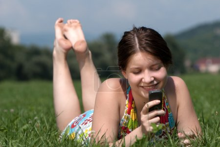Girl speaks by mobile phone against summer green nature