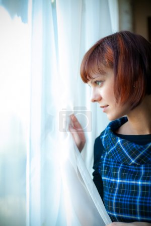Photo for Young woman looking through the window, she is waiting for somebody or something, or maybe watching someone - Royalty Free Image