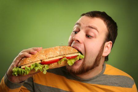 Photo for Funny guy eating hamburger on green background - Royalty Free Image