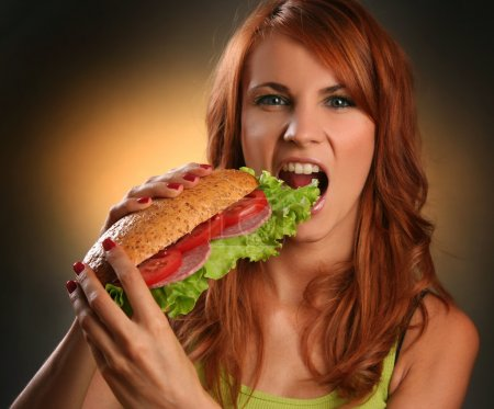 Photo for Young woman eating fast food - Royalty Free Image