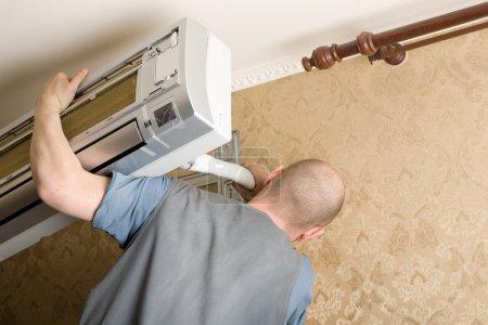 Photo pour Maître de l'air conditionné installe un nouveau climatiseur dans l'appartement. - image libre de droit