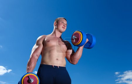 Photo for Strong man doing exercises outdoor with dumbbells - Royalty Free Image