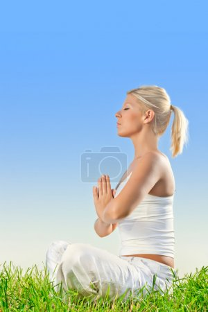 Pretty young woman doing yoga meditation exercising outdoors