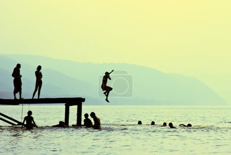 Photo for Silhouettes of kids who jump off dock on the lake at sunset. - Royalty Free Image