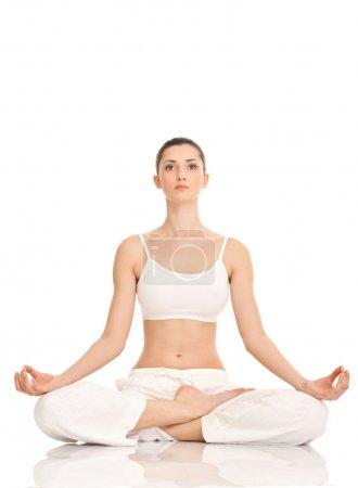 Photo pour Jeune femme pratiquant le yoga en position lotus, isolée sur blanc - image libre de droit