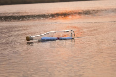 Photo for Message in a bottle buried in sand on the beach - Royalty Free Image