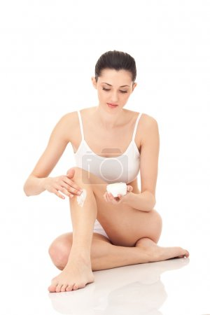 Woman putting cream on leg