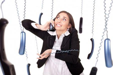 Foto de Secretaria joven torpe con teléfono, respondiendo a un montón de llamadas al mismo tiempo, aislado en blanco - Imagen libre de derechos