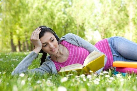 Photo pour Fille couchée sur l'herbe avec des fleurs dans le parc, lire le livre et écouter de la musique à travers casque - image libre de droit