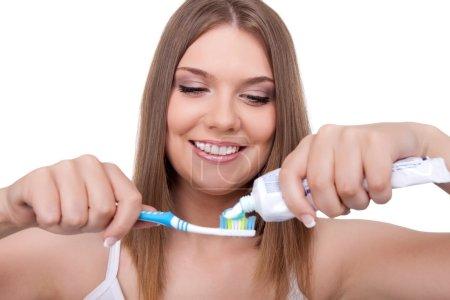 Photo pour Jeune femme mettre de la pâte sur une brosse à dents, isolé sur fond blanc - image libre de droit
