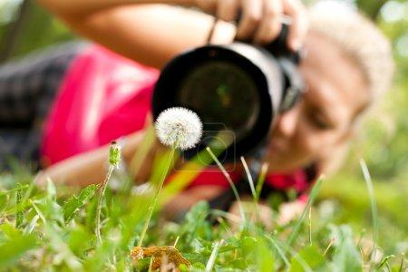 Photo pour Photo femme avec appareil photo, prendre une photo de fleur - image libre de droit