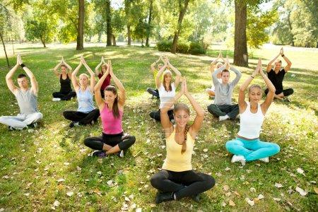 Photo pour Grand groupe d'adultes participant à un cours de yoga à l'extérieur dans le parc - image libre de droit
