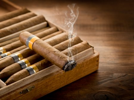 Smoking cuban cigar over box on wood background