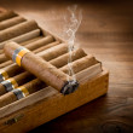 Smoking cuban cigar over box on wood background...
