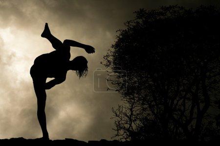 Photo pour Homme pratique les arts martiaux High Kick Silhouette sur fond de ciel orageux - image libre de droit