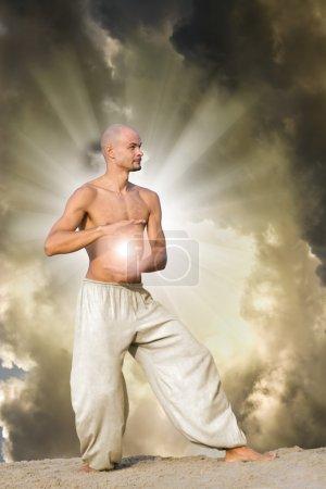 Photo pour L'homme pratique le Tai tenant une boule d'énergie avec un ciel nuageux dramatique et des rayons de soleil en arrière-plan - image libre de droit